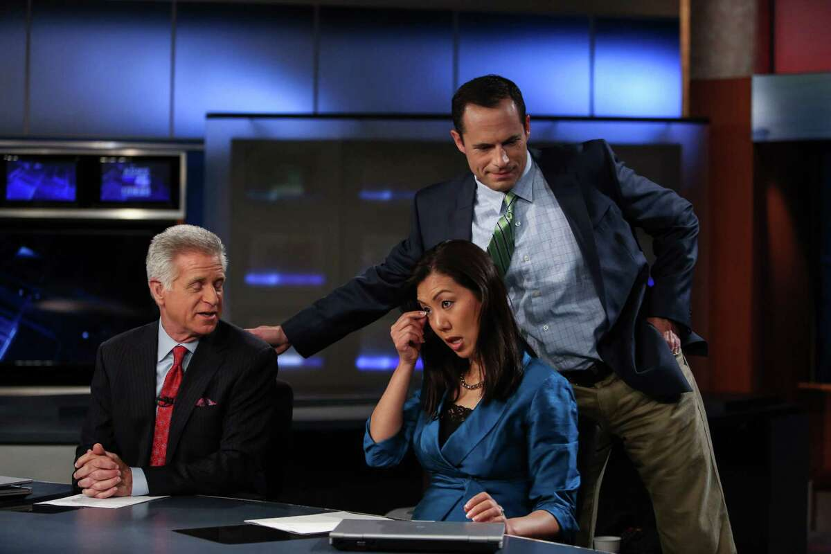 Mike Ferreri thanks Dan Lewis at the conclusion of Lewis' final 6 p.m. newscast as Mary Nam tries to hold back tears. Photographed on Wednesday, May 21, 2014.