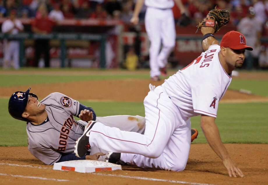 The ninth inning was double trouble for Astros rookie George Springer, left, who was picked off first base and in pain after being tagged by Albert Pujols. Photo: Chris Carlson, STF / AP