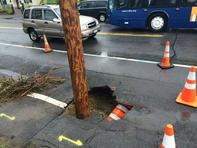 A small sink hole opened on Deleware Avenu in Bethlehem after a downpour that flooded the busy street on Thursday, May 22, 2014. (Will Waldron / Times Union)