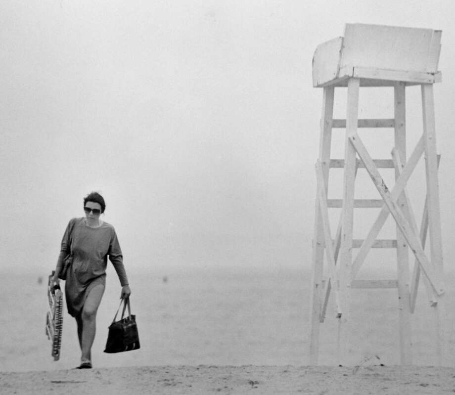 Mary Horesco of Stamford walks off of Cummings Beach after the city's health director Dr. Andrew McBride closed the city's beaches after 300,000 gallons of raw sewage spilled into Long Island Sound in Darien on May 26, 1989. Photo: File Photo/John Voorhees / Stamford Advocate File Photo