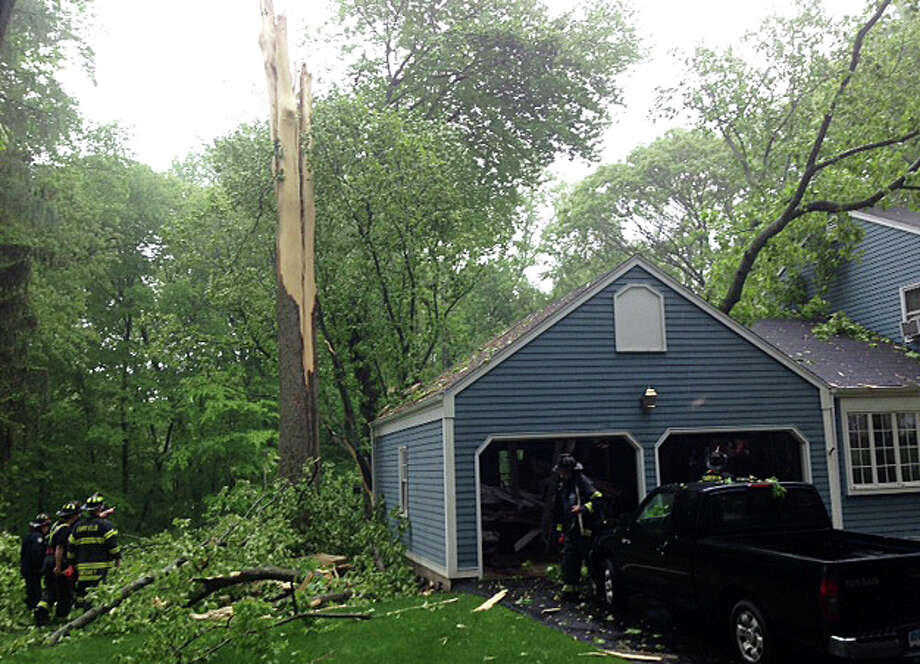Firefighters survey damage caused when a tree struck by a lightning bolt Thursday morning toppled onto a Surrey Lane house and garage. Photo: Fairfield Fire Department / Fairfield Citizen