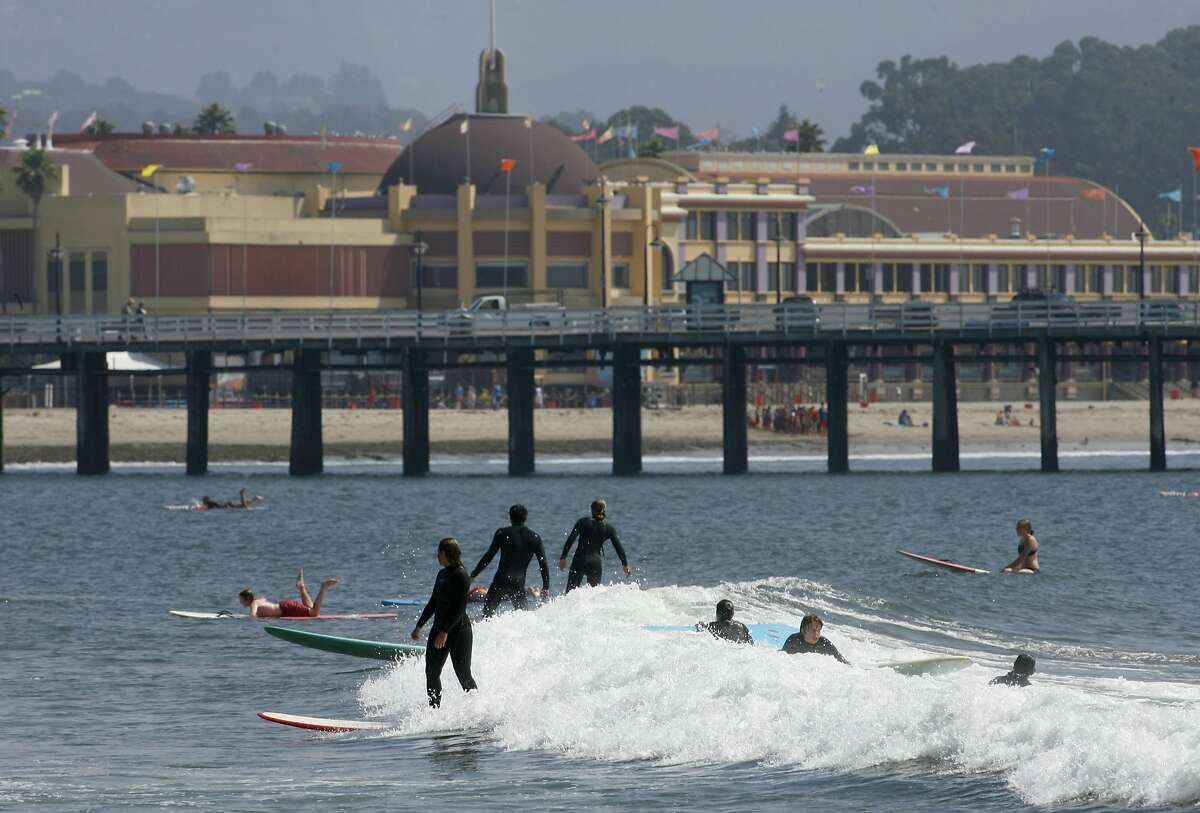 In this file photo, beginning surfers have a go at the waves at Cowell Beach with the Boardwalk looming above them.
