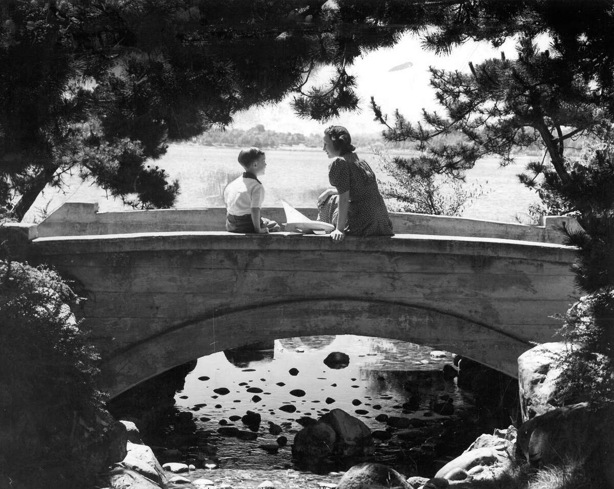 A woman and boy on a bridge at Green Lake in 1940. Photo by Francis Jackson