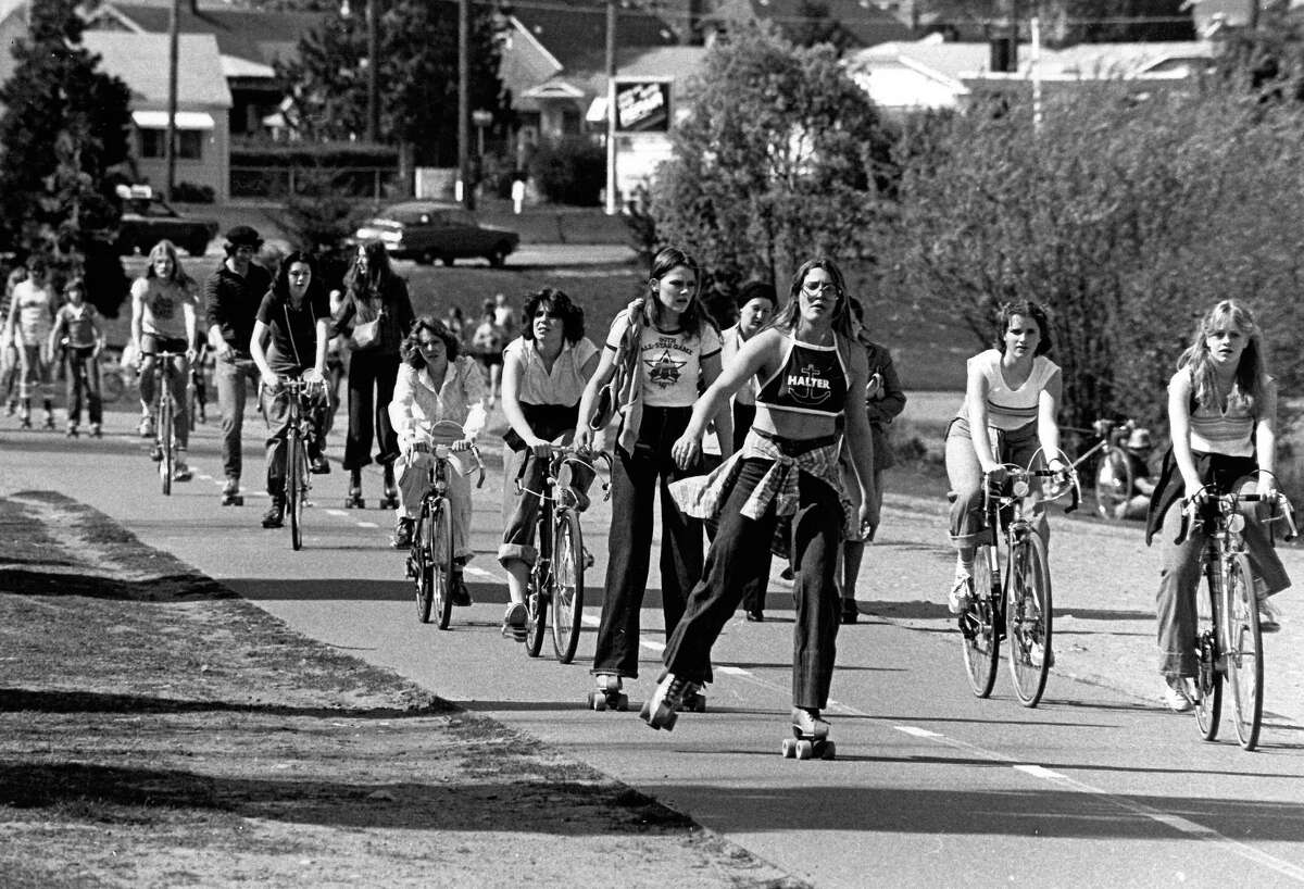 Original photo caption: Big wheels, small whees propel the natives of Seattle around the Green Lake in search of the mythical suntan they hear so much about from other parts of the country. Photo by Tom Brownell. April 22, 1979.