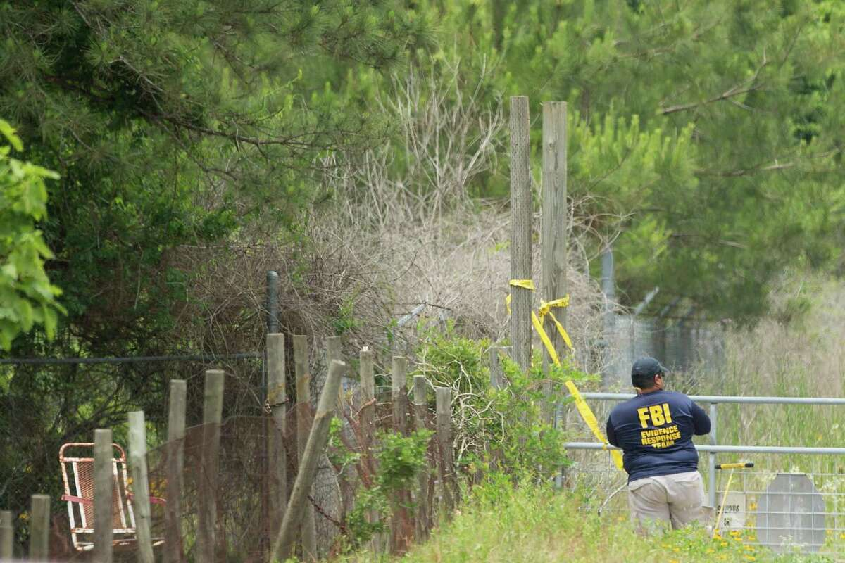 Law enforcement officers investigate the scene in rural Montgomery County where the FBI arrested the alleged killer of Gelareh Bagherzadeh Thursday, May 22, 2014, in Conroe. Bagherzadeh was shot to death outside her Galleria area town home in January of 2012.