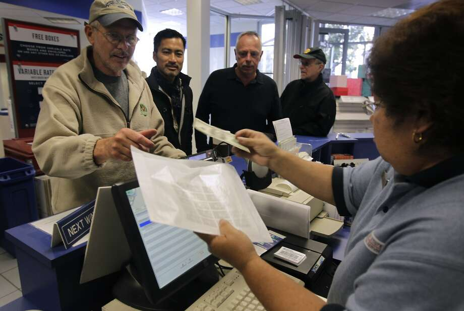 John Carr (left) purchases about $100 worth of the new Harvey Milk stamp at the Castro neighborhood post office in San Francisco, Calif. on Thursday, May 22, 2014. Carr has lived in the neighborhood since 1979, not long after Milk's assassination. The U.S. Postal Service honored the slain gay rights leader with a commemorative stamp featuring a photograph taken by Daniel Nicoletta Photo: Paul Chinn, The Chronicle