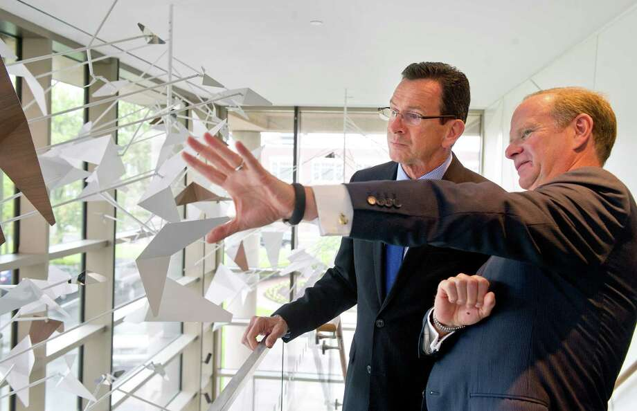 Connecticut Governor Dannell Malloy, left, and Starwood Chief Administrative Officer Kenneth Siegel, right, talk in the lobby at Starwood Hotels & Resorts in Stamford, Conn., on Thursday, May 22, 2014, before announcing Starwood will add 340 new employees in Stamford. Photo: Lindsay Perry / Stamford Advocate