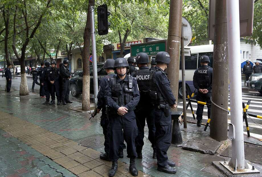 Armed policemen stand guard near the site of several explosions in Urumqi, Xinjiang region. Photo: Andy Wong, Associated Press