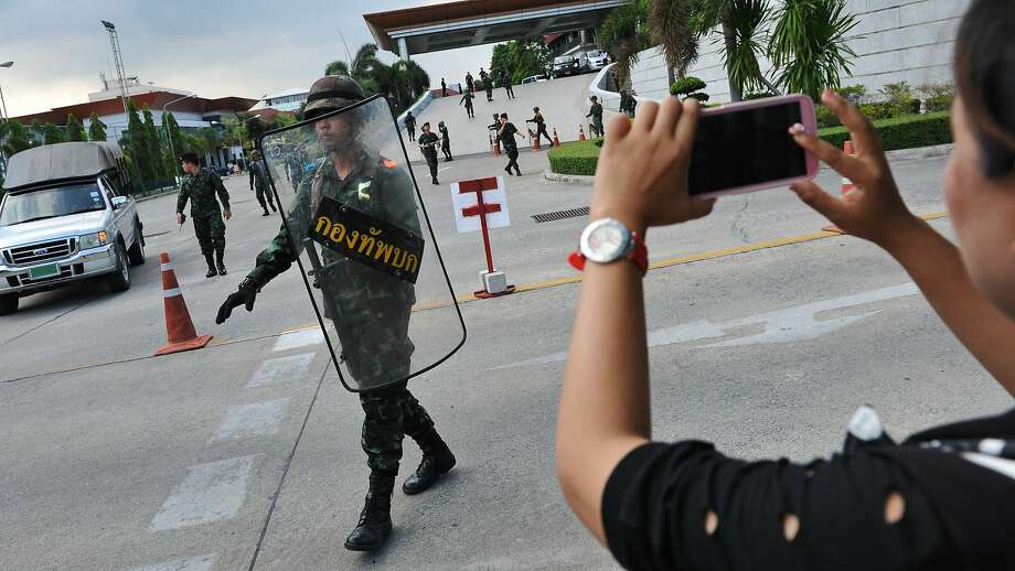 A woman uses a cell phone to capture soldiers securing the grounds of the venue for peace talks between pro- and anti-government groups in Bangkok. Photo: Rufus Cox, Getty Images