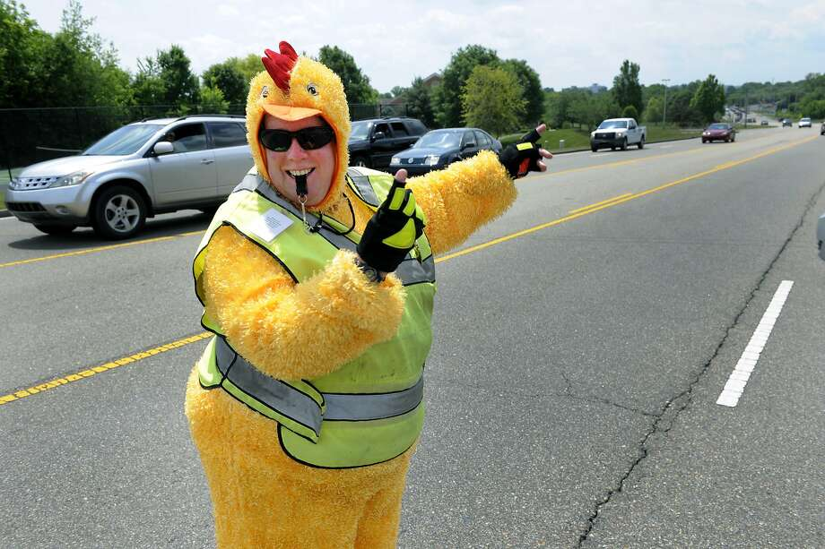 """Why did the chicken cross the road? To direct traffic:A costumed Sarah Kibble safeguards children on the last day of school at Cedar Bluff Elementary and Middle School in Knoxville, Tenn. """"My boss said as long as it was a bright outfit and I didn't cover my face, it was okay,"""" said Kibble, the security officer for the schools. Photo: Michael Patrick, Associated Press"""