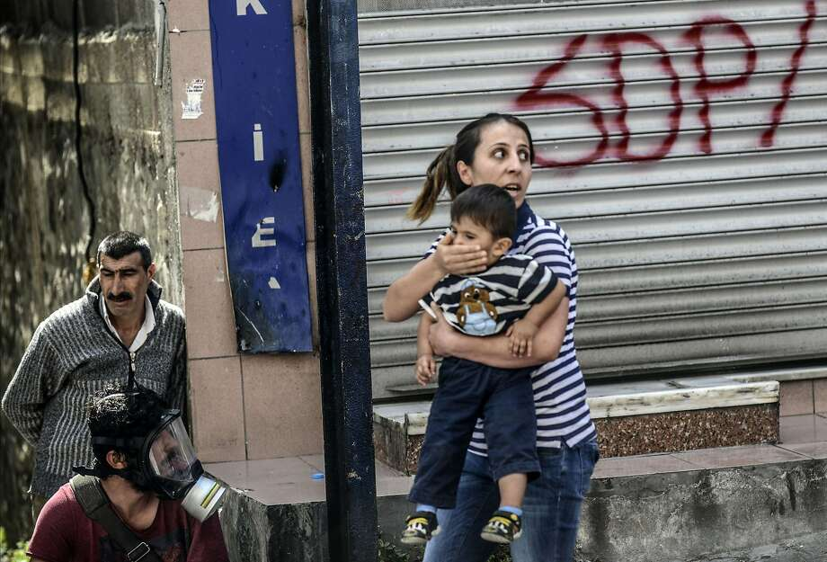A mother and child try to escapestreet fighting between Turkish riot police and protesters in the Okmeydani district of Istanbul. One man was injured when police fired tear gas and water cannon to disperse demonstrators angry about the Soma mining disaster, which claimed 301 lives. Photo: Bulent Kilic, AFP/Getty Images