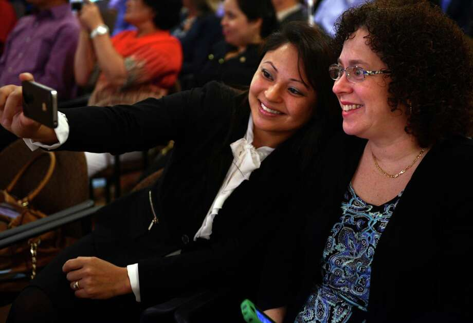 Tatiana Coelho, of Trumbull, originally from Brazil, takes a photograph with Ellen Belitzky, of Fairfield,  Thursday, May 22, 2014, before being sworn in as an American citizen during a Naturalization Ceremony at the Fairfield Museum and History Center in Fairfield, Conn. Coelho was an au pair for Belitzky's family when she first came to the US. Photo: Autumn Driscoll / Connecticut Post