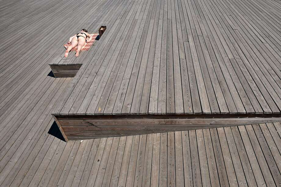 A sunbather enjoysthe 80-degree weather along Moskva River in Moscow. Photo: Kirill Kudryavtsev, AFP/Getty Images