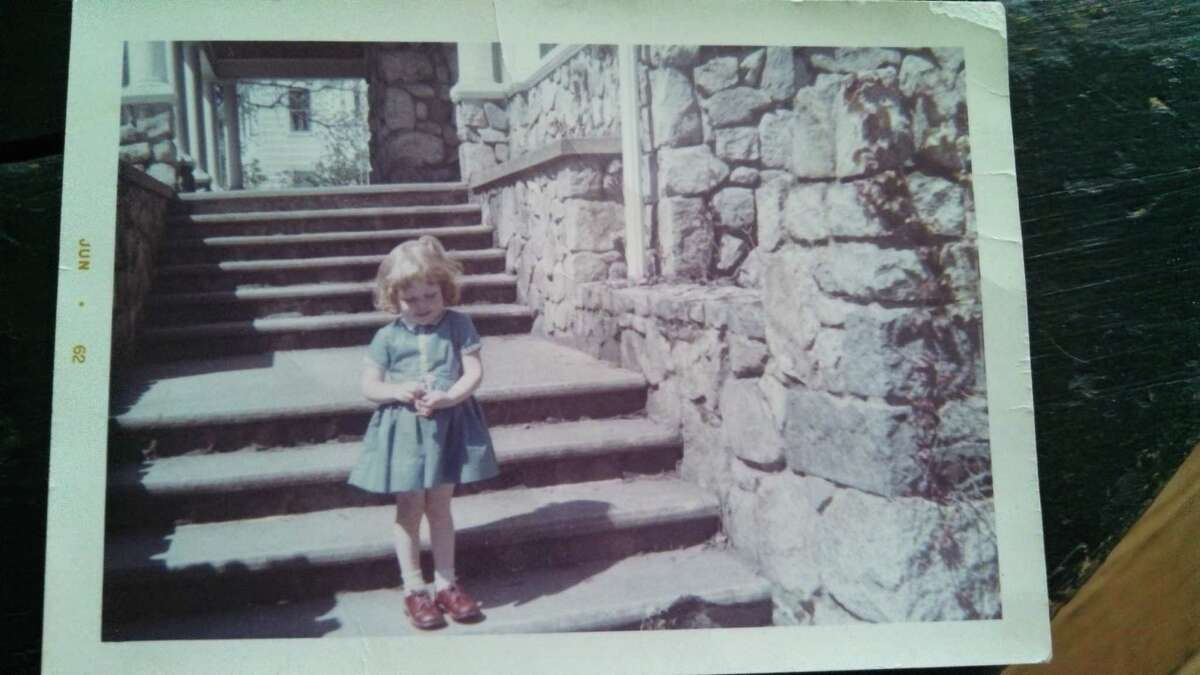 Patty Lane, age 4, on the steps of her first historic home in Hingham, Mass.
