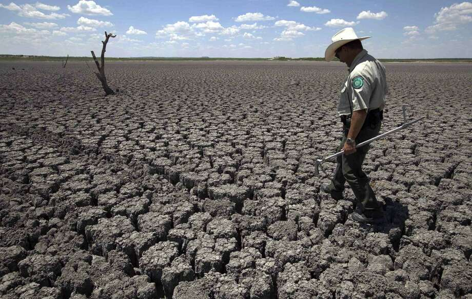Texas State Park police officer Thomas Bigham walks across the cracked lake bed of O.C. Fisher Lake in San Angelo. Does he see the benefits of global warming? Photo: Tony Gutierrez, Associated Press / AP