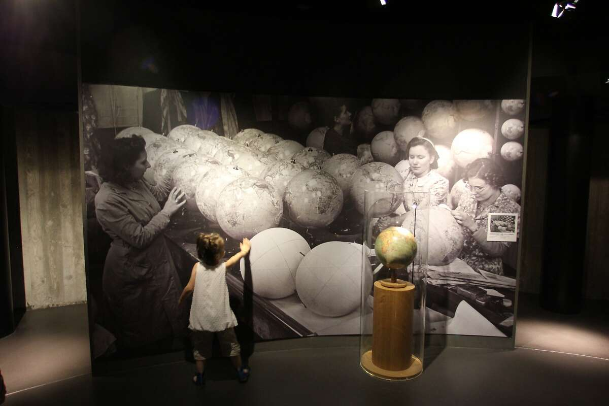 A child touches a photo at the Caen Memorial of globe factory workers applying new boarders to reflect the expansion of the Third Reich.