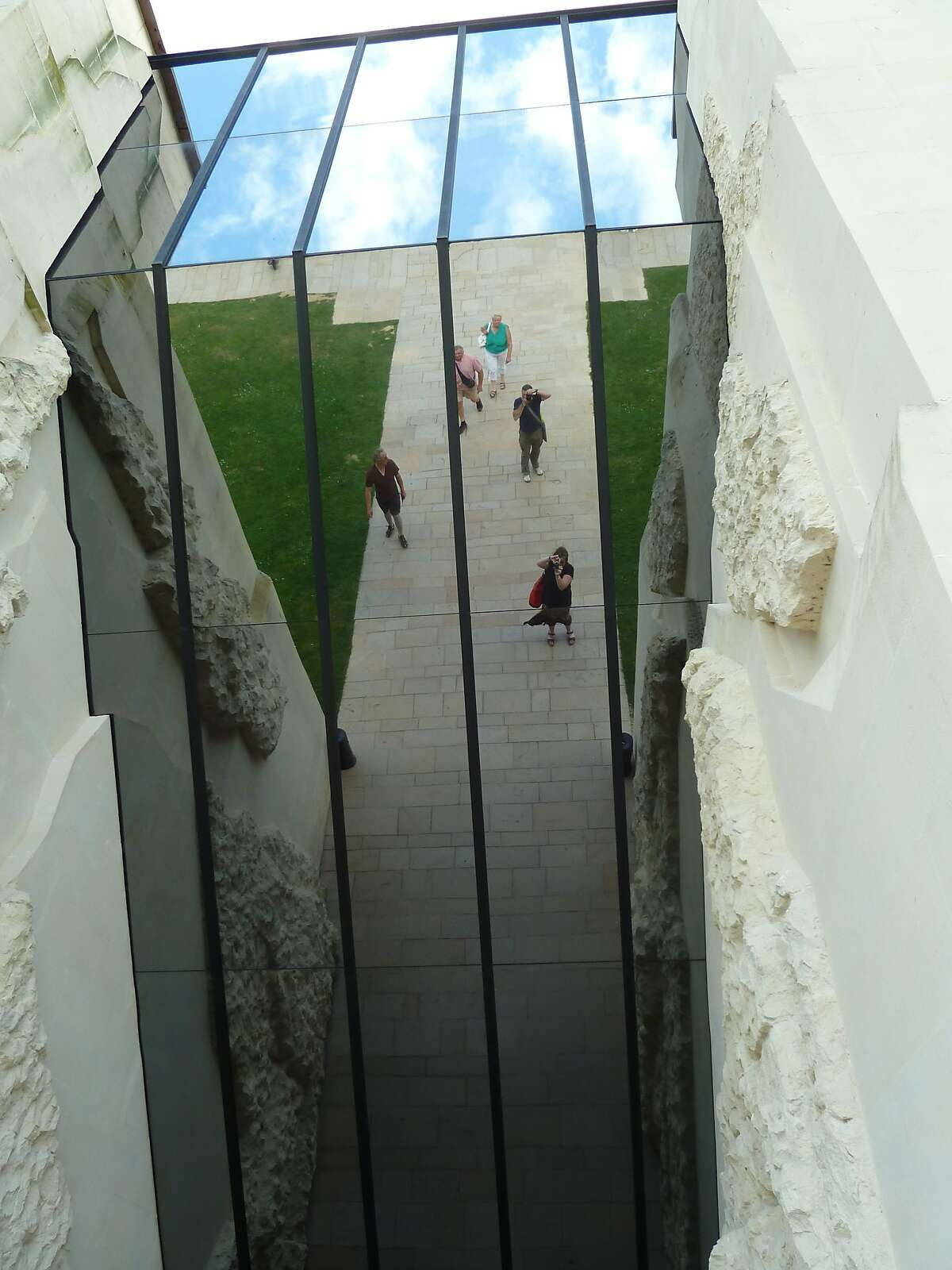 Visitors are reflected in the mirrors of the rift-like entrance at the Caen Memorial Centre for History and Peace. The museum is a few miles from the some of the landing beaches used in the Invasion of Normandy in WW II.