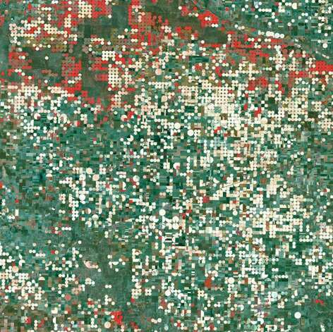 "Garden City, Kansas – Center-pivot irrigation systems created the circular patterns near Garden City. The red circles indicate irrigated crops of healthy vegetation, and the light-colored circles denote harvested crops. Photo: Boyd, John, Source: ""Earth As Art,"" Published By NASA"