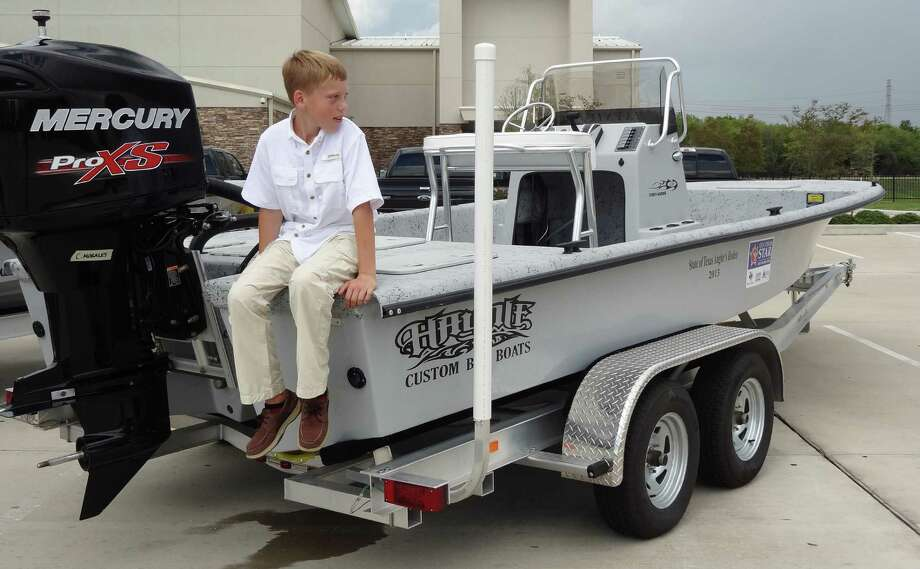Caleb Morales, 10, of Danbury, sits atop the 23-foot boat and trailer he won last year with a tagged redfish. Because of his age, Morales was awarded a $20,000 scholarship by Ford instead of the pickup that was also part of his prize package. Photo: Courtesy Photos