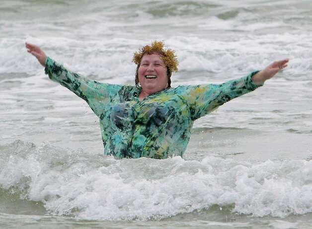 Elena Smith frolics in the surf with a patch of seaweed on her head near 19th street Thursday, May 22, 2014, in Galveston. Photo: James Nielsen, Houston Chronicle / © 2014  Houston Chronicle