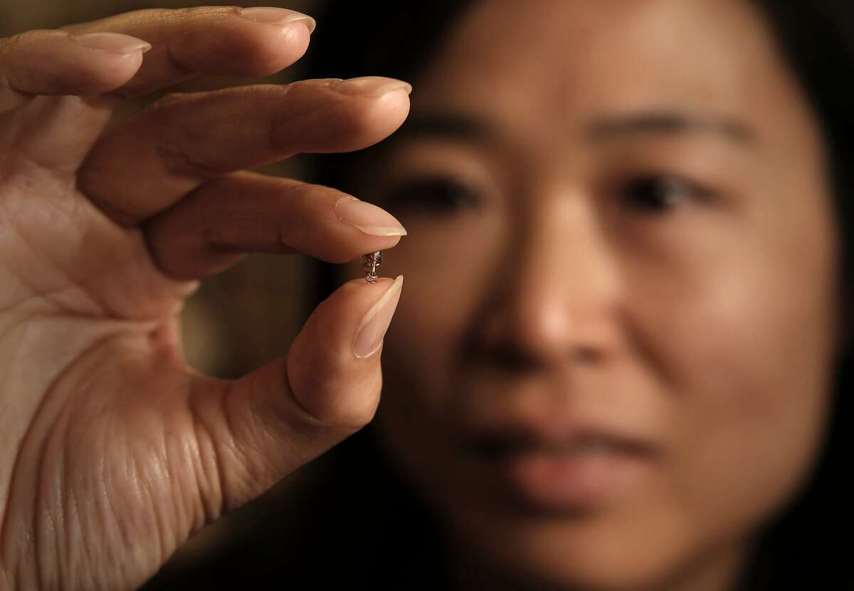 Professor Ada Poon holds the micro implant device at their research laboratory on the Stanford campus, in Palo Alto, Calif., on Wednesday May 21, 2014. Stanford electrical engineer, Professor Ada Poon, has invented a way to wirelessly transfer power deep inside the body, and then use this power to run tiny electronic medical gadgets such as pacemakers, nerve stimulators or new sensors/devices yet to be developed.
