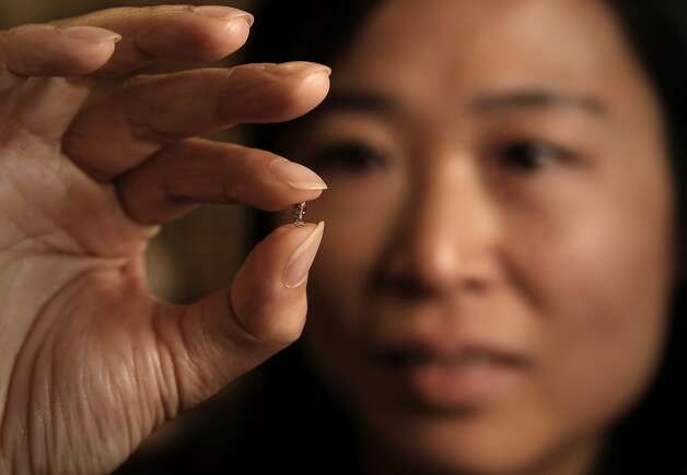 Ada Poon, a Stanford electrical engineer, holds a device that can be implanted in the body and controlled wirelessesly. Photo: Michael Macor, The Chronicle