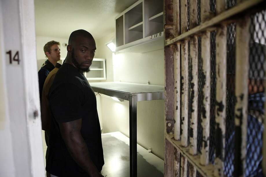 Mahala Wiggins (right), Cal's strength and conditioning coach, and quarterback Jared Goff survey the inside of a cell at San Quentin State Prison. Photo: Michael Short, The Chronicle