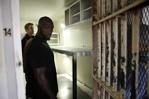 Strength and conditioning coach Mahala Wiggins, right,  and quarterback Jared Goff get an inside look at a cramped cell as Cal Bears football players make a visit to San Quentin State Prison in San Quentin, CA, Saturday May 3, 2014.