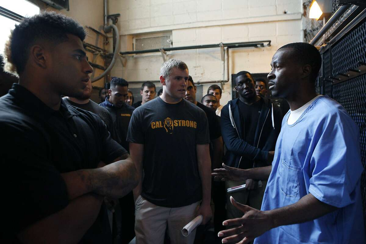 (L-R) Cal Bears football players Edward Tandy, Cormac Craigie and Jonathan Johnson listen to inmate Sha Wallace as he describes how the shower area works during the teams visit to San Quentin State Prison in San Quentin, CA, Saturday May 3, 2014.