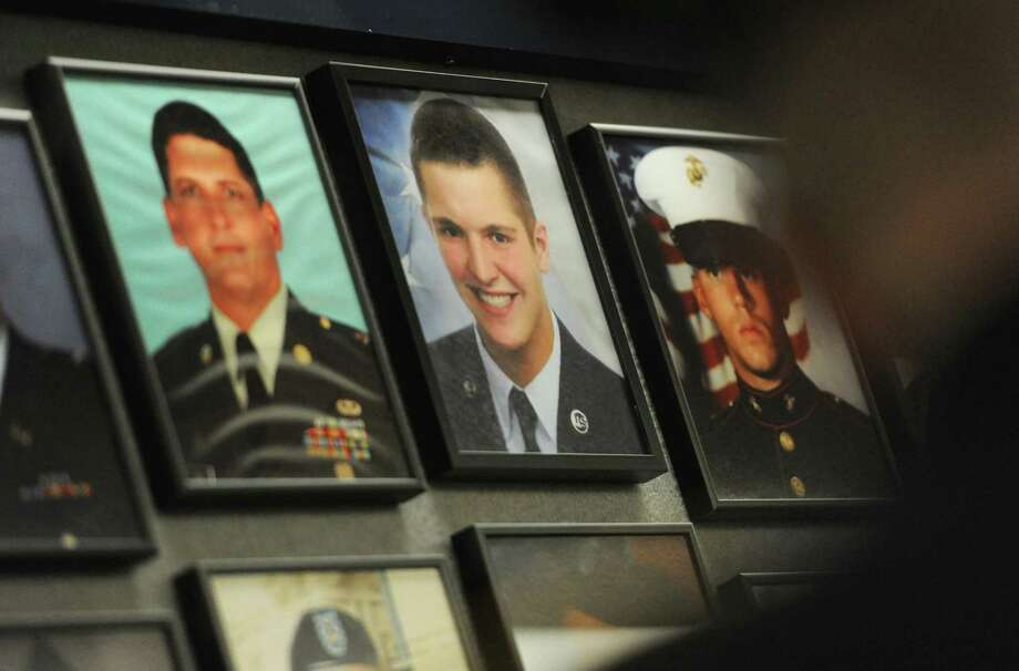 "A photo of U.S. Air Force Staff Sgt. Todd James ""T.J."" Lobraico, center, hangs on the Wall of Honor with other Connecticut soldiers killed in action during the Connecticut Wall of Honor Ceremony at the Legislative Office Building in Hartford, Conn. Thursday, May 22, 2014.  This year's ceremony honored Lobraico, 22, of New Fairfield, who was killed in action in Afghanistan on Sept. 5, 2013.  Lobraico's photo was placed on the wall with other Connecticut armed forces member killed in Afghanistan and Iraq since Sept. 11, 2001. Photo: Tyler Sizemore / The News-Times"