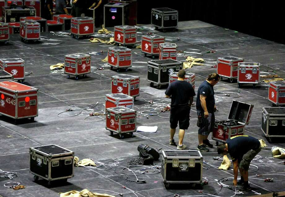 Workers install stage and lighting equipment Thursday for the Journey concert at the AT&T Center. Photo: William Luther, San Antonio Express-News / © 2014 San Antonio Express-News