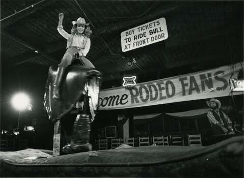Lynn Wyatt, one of the chairmen of the benefit premiere of Urban Cowboy,  rides the mechanical bull at Gilley's Club. Photo: Fred Bunch, Houston Chronicle