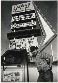 "04/17/1987 - Gilleyrat Gator Conley stands next to the sign at Gilley's Club.  Gator was featured in the movie ""Urban Cowboy"". Photo: Carlos Rosales, Houston Chronicle"