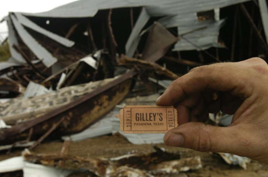 Gilley's: Old ticket for Gilley's nightclub in Pasadena, Texas with the demolition of last standing structures in background. The Pasadena school district acquired the property and plans to build a school on the site.  Photo by Carlos Antonio Rios Houston Chronicle     HOUCHRON CAPTION (11/09/2005) SECNEWS COLORFRONT:  A ticket stub found Tuesday became a souvenir as Gilley's, the legendary Pasadena nightclub, was torn down at the behest of the Pasadena school district. Photo: Carlos Antonio Rios, Houston Chronicle