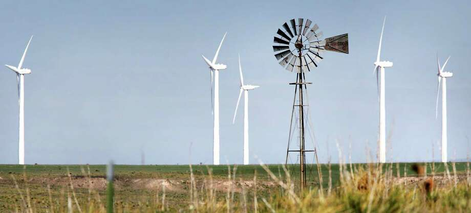 An old windmill that pumps water for cattle is framed by the new wind turbines that produce electricity, along Highway 287 just north of Amarillo. A California-based energy company hopes to export the state's wind power to other parts of the country. Photo: Express-News File Photo / © 2012 San Antonio Express-News