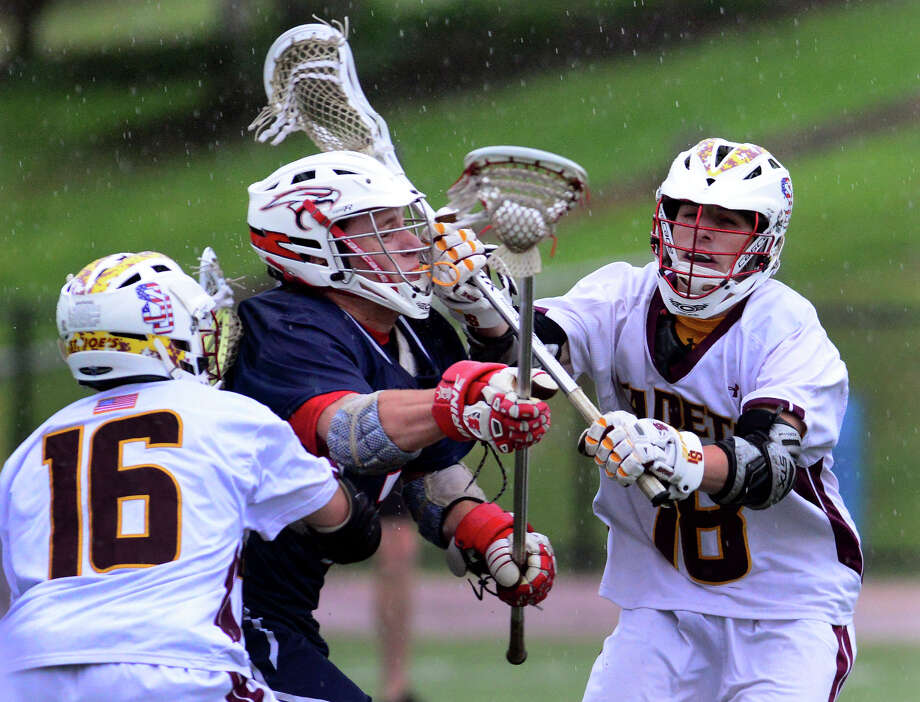 St. Joseph's Mike Brennan, right, and Rick Giordano put the squeeze on Avon's Sean Neagle, during boys lacrosse action in Trumbull, Conn. on Thursday May 22, 2014. Photo: Christian Abraham / Connecticut Post