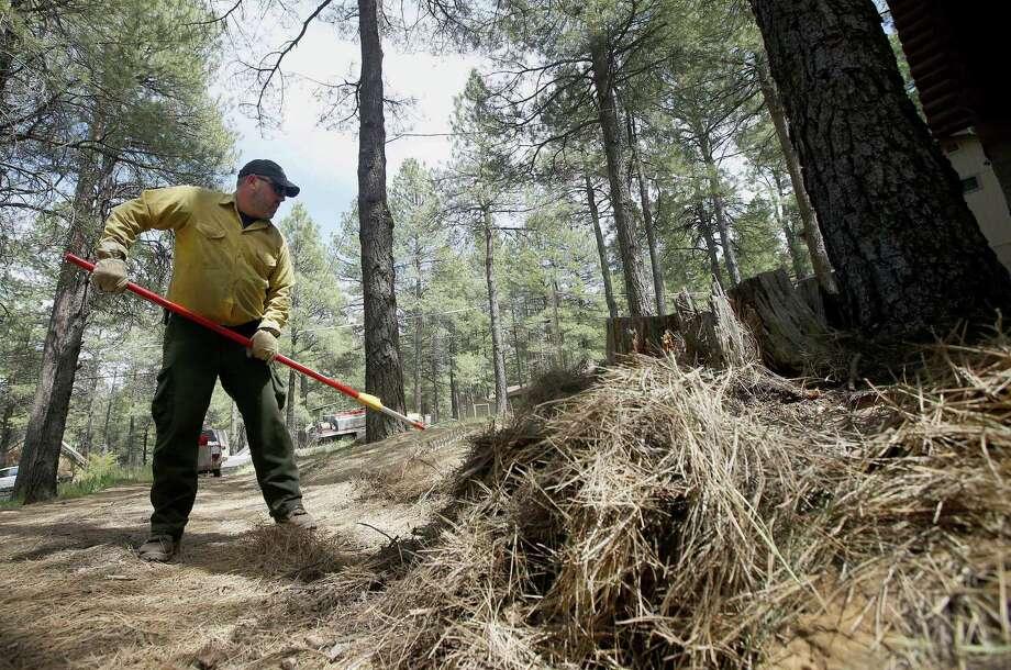John Rheinboltpulls ground clutter away from a home as the Slide Fire burns nearby in Kachina Village, Ariz. Photo: Associated Press / AP