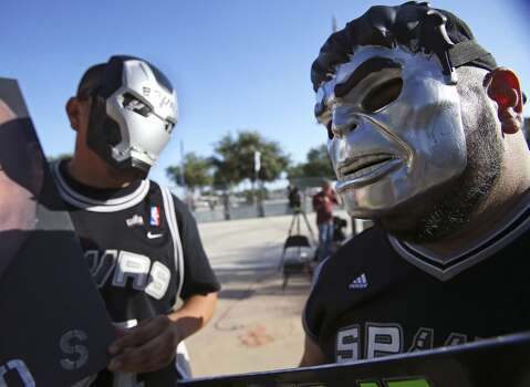 Juan Ramirez (left) and David Galan show up in black with intimidating masks as the Spurs fans start to party before the opener against the Thunder at the AT&T Center on May 19, 2014. Photo: Tom Reel, San Antonio Express-News