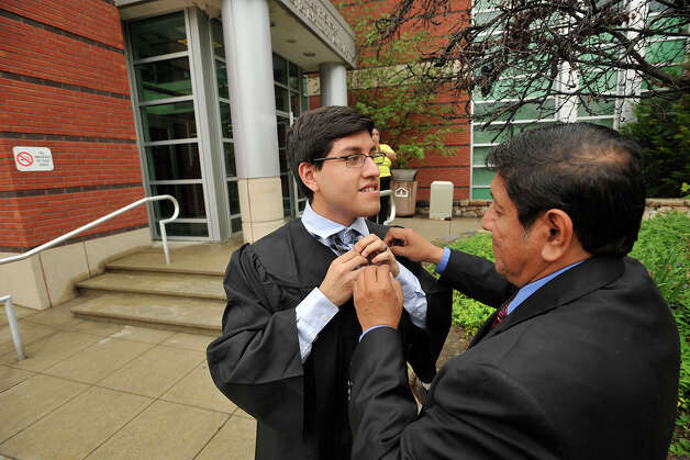 Carlos Moran helps his son, David Moran, of Stratford, tie his tie before the Norwalk Community College commencement ceremony at the community college in Norwalk, Conn., on Thursday, May 22, 2014. Photo: Jason Rearick / Stamford Advocate