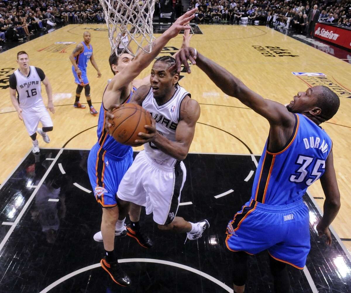 Western Conference Finals, Game 1 - May 19, 2014: Spurs 122, Thunder 105 San Antonio Spurs' Kawhi Leonard shoots between Oklahoma City Thunder's Steven Adams (left) and Kevin Durant during second half action of Game 1 in the Western Conference Finals Monday, May 19, 2014, at the AT&T Center.