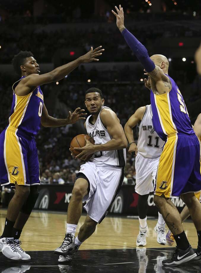 San Antonio Spurs' Cory Joseph goes between Los Angeles Lakers' Nick Young, left, and Robert Sacre during the second half at the AT&T Center, Wednesday, April 16, 2014. The Lakers won 113-100. Photo: Jerry Lara, San Antonio Express-News