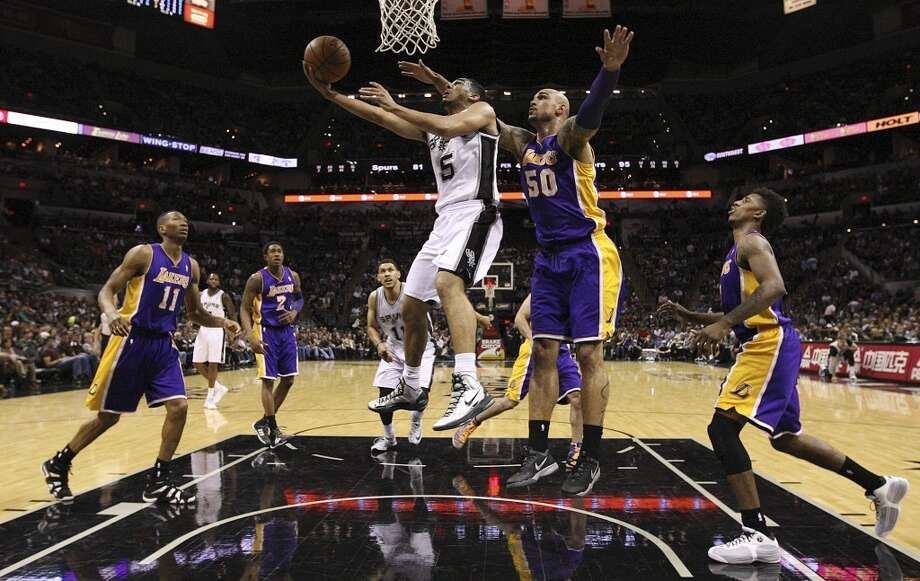 San Antonio Spurs' Cory Joseph goes for two as Los Angeles Lakers' Robert Sacre defends during the second half at the AT&T Center, Wednesday, April 16, 2014. The Lakers won 113-100. Photo: Jerry Lara, San Antonio Express-News