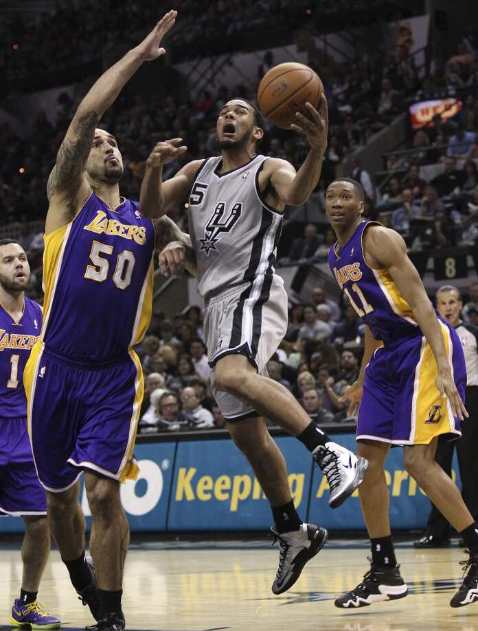 Spurs' Cory Joseph (05) drives to the basket against Los Angeles Lakers' Robert Sacre (50) in the second half at the AT&T Center on Friday, Mar. 14, 2014. Photo: Kin Man Hui, San Antonio Express-News