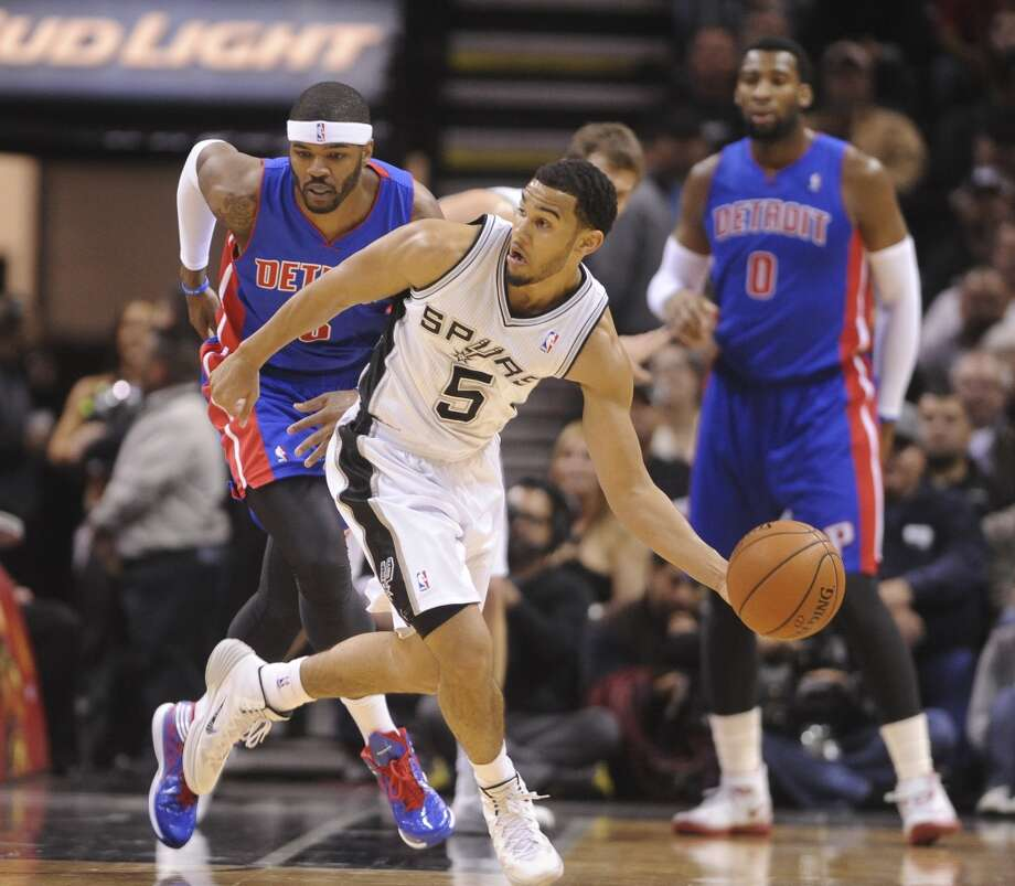 Cory Joseph (5) of the San Antonio Spurs steals the ball from Josh Smith of the Detroit Pistons during NBA action in the AT&T Center on Wednesday, Feb. 26, 2014. Photo: Billy Calzada, San Antonio Express-News
