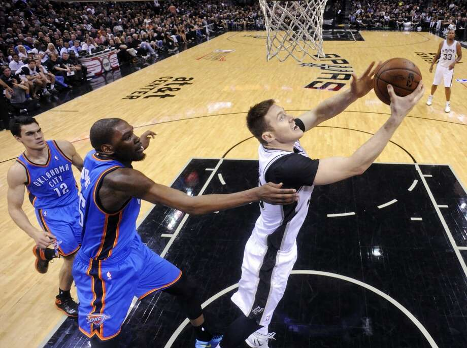 San Antonio Spurs' Aron Baynes shoots around Oklahoma City Thunder's Kevin Durant as Steven Adams moves in on the play during second half action of Game 1 in the Western Conference Finals Monday May 19, 2014 at the AT&T Center. The Spurs won 122-105. Photo: Edward A. Ornelas, San Antonio Express-News