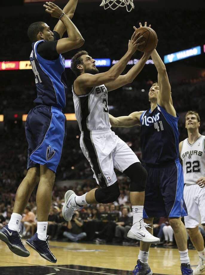 San Antonio Spurs' Marco Belinelli drives between Dallas Mavericks' Brandan Wright, left, and Dirk Nowitzki during the first half of game two in the first round of the Western Conference Playoffs at the AT&T Center, Wednesday, April 23, 2014. Photo: Jerry Lara, San Antonio Express-News