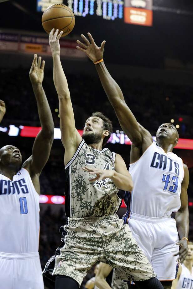 San Antonio Spurs' Marco Belinelli shoots between Charlotte Bobcats' Bismack Biyombo (left) and Charlotte Bobcats' Anthony Tolliver during first half action Friday Feb. 28, 2014 at the AT&T Center. Photo: Edward A. Ornelas, San Antonio Express-News
