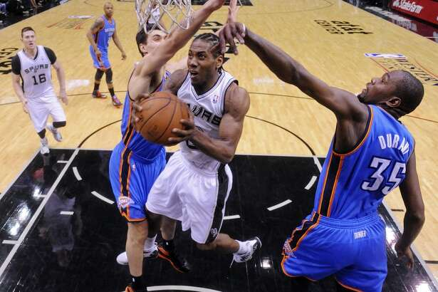 San Antonio Spurs' Kawhi Leonard shoots between Oklahoma City Thunder's Steven Adams (left) and Kevin Durant during second half action of Game 1 in the Western Conference Finals Monday May 19, 2014 at the AT&T Center. The Spurs won 122-105.