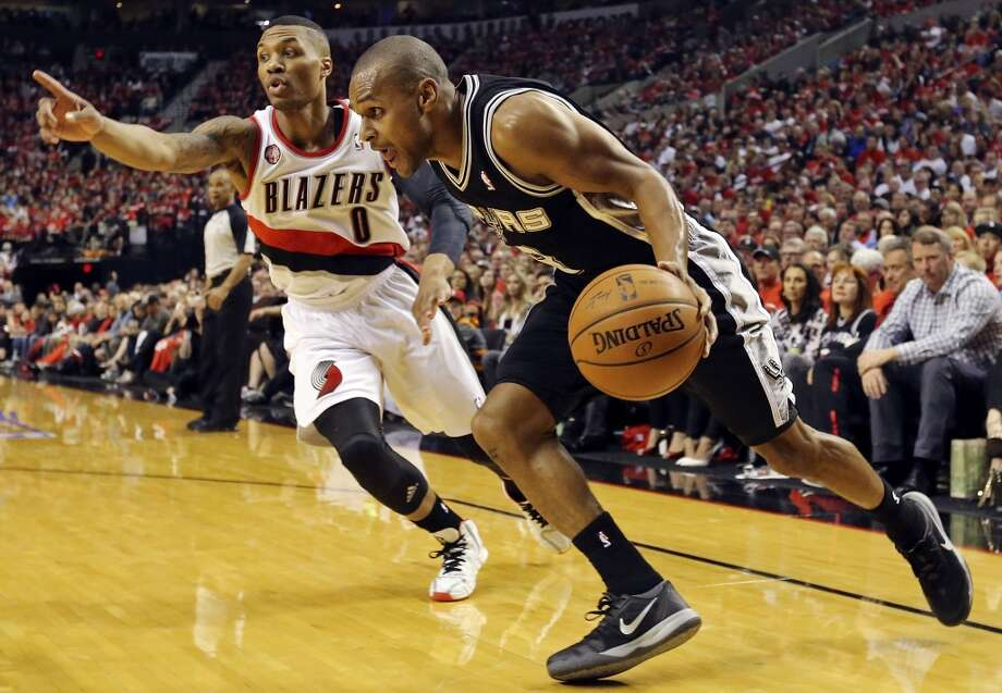 San Antonio Spurs' Patty Mills drives around Portland Trail Blazers' Damian Lillard during first half action of Game 3 in the Western Conference semifinals Saturday May 10, 2014 at the Moda Center in Portland, OR. Photo: Edward A. Ornelas, San Antonio Express-News