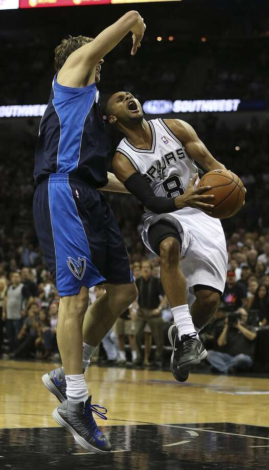 San Antonio Spurs' Patty Mills drives the ball as Dallas Mavericks' Dirk Nowitzki defends during the first half of game two in the first round of the Western Conference Playoffs at the AT&T Center, Wednesday, April 23, 2014. Photo: Jerry Lara, San Antonio Express-News